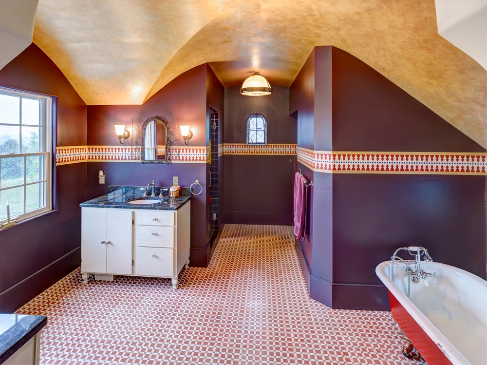 The master bath of this custom-built home has unusual details in both the ceiling and configuration of the floor. A walk-in shower was installed with a walled surround. A freestanding tub was placed near the shortest wall. Two single sink vanities were placed on each side of a window, which provides natural light.