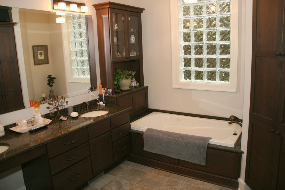 This master bath includes a double sink vanity with a kneehole and a side with storage drawers for grooming supplies. There is a soaking tub with a custom built deck. Privacy and natural light in the room are provided by a glass block window.