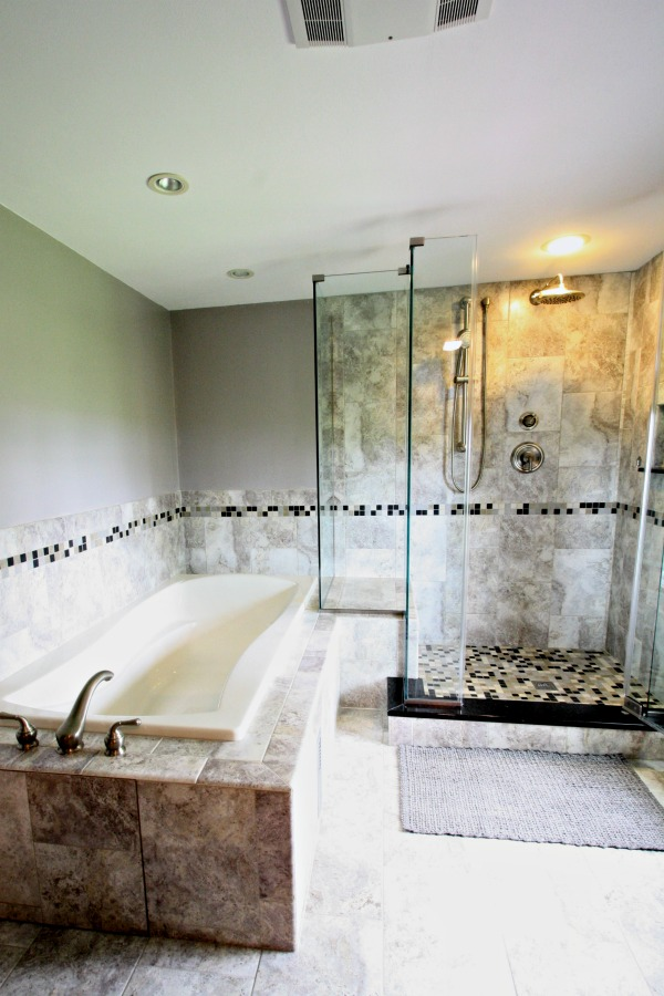 This master bath remodel features a custom glass enclosed walk-in shower and ceramic tile on the floor, walls and tub surround. The ceramic wall tile in the shower extends from the shower floor to the ceiling, which creates an illusion of space. Border tile integrates the shower and soaking tub areas.