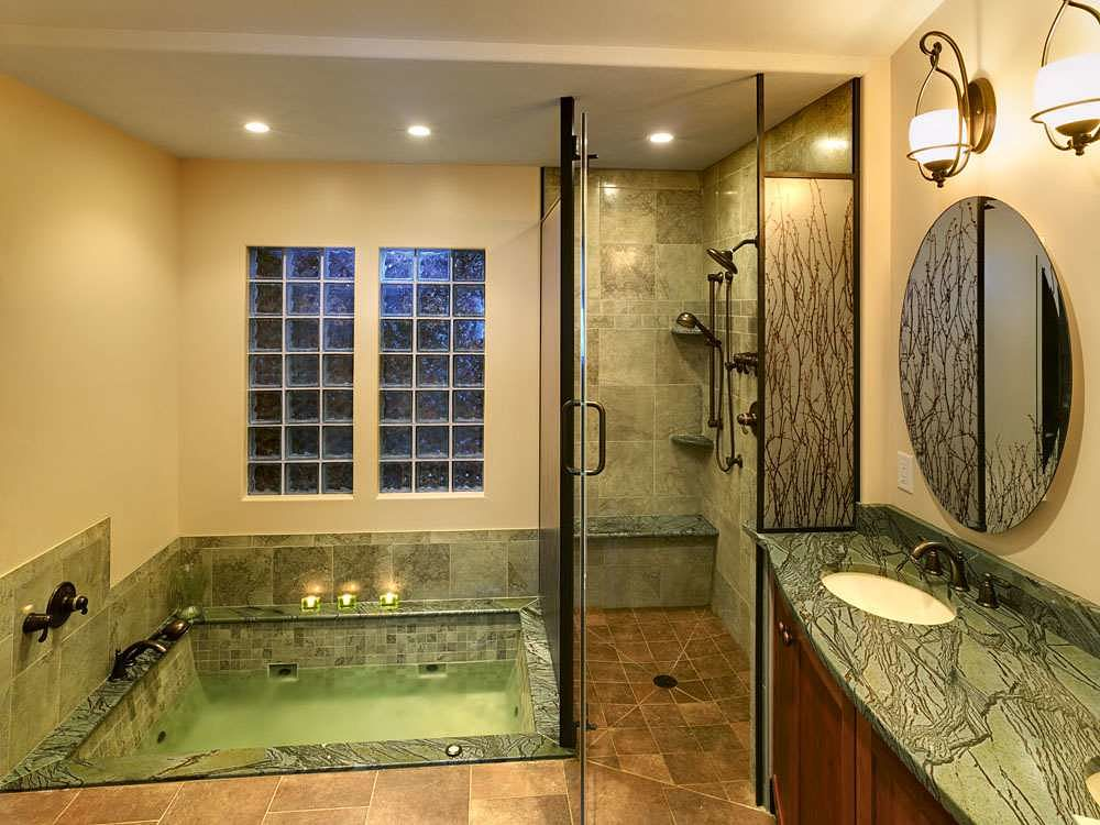 Multiple showerheads and granite tile with a seating area add to the luxury of this walk-in shower.