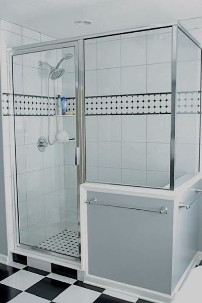 Walk-in shower with glass enclosure.