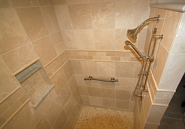 "The large walk-in shower is a ""room within a room"". Stunning details include the river rock floor tile that provides a non-slip surface for users. Matte finish marble tiles were selected for the interior. The border is 3-by-6 inch tile and listello accent tile. Carrera marble tops the wall and creates the lower edge of the wall niche."