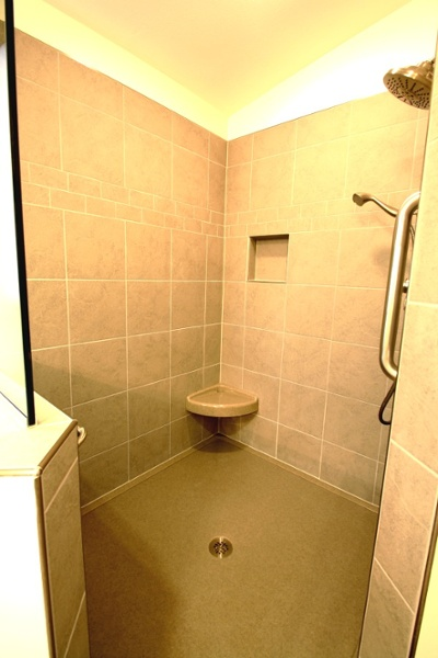 A low threshold and custom onyx floor are installed in the tile walk-in shower. A custom-fitted shower seat was built into a corner and a towel bar was installed on the far left of the stall.