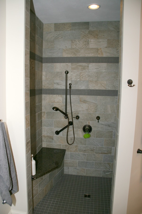 This doorless shower in the master bathroom is equipped with a handheld showerhead, lowered controls and a shower bench.