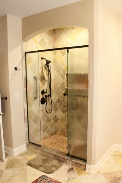 Design elements of this custom walk-in shower include an arched entryway and granite trim at the threshold. Moisture resistant sheetrock was used for both sides of the arched header. Framed embossed glass panels with a centered door provide easy access and privacy. There is a corner shower seat and both a wall mounted showerhead and handheld spray. Mosaic tile was used for the shower base. The shower enclosure tile is a natural stone wall set in a diagonal pattern.