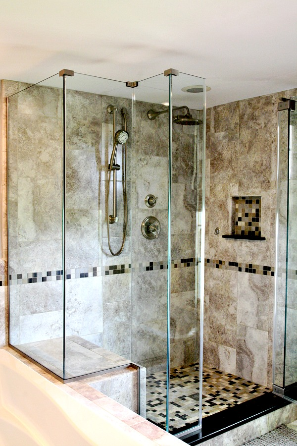 This custom mud set shower features ceramic tile floor and walls in a classic color palate. The glass surround provides an open feel to the space. A custom niche was created in the wall to hold soaps and shampoo. The seating area complements the soaking tub. The hand-held shower and wall mount rainfall showerhead and fixtures are brushed nickel.