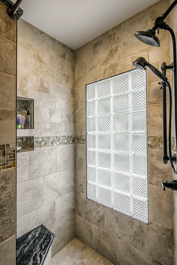 This walk-in shower has a glass block window that brings natural light into the space. The art glass mosaic accent tile has a pinwheel pattern. Universal design features include two showerheads, a grab bar and lever handle faucet fixture.