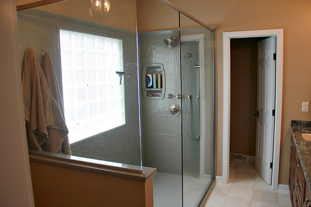 "This walk-in shower without doors has a glass surround with a kneewall. The window is diamond cut glass set on a smooth plane within the shower so that water will not accumulate on the framing. A custom Onyx shower base with a low threshold and Onyx shower wall panels with a stone tile gloss finish (Slate Stone 12-by-12 inch tile design in ""Spanish Moss"") were used for the shower. The shower includes a wall niche, a shower seat, a wall-mounted rainfall showerhead, a handheld showerhead and a sealed can light in the ceiling."