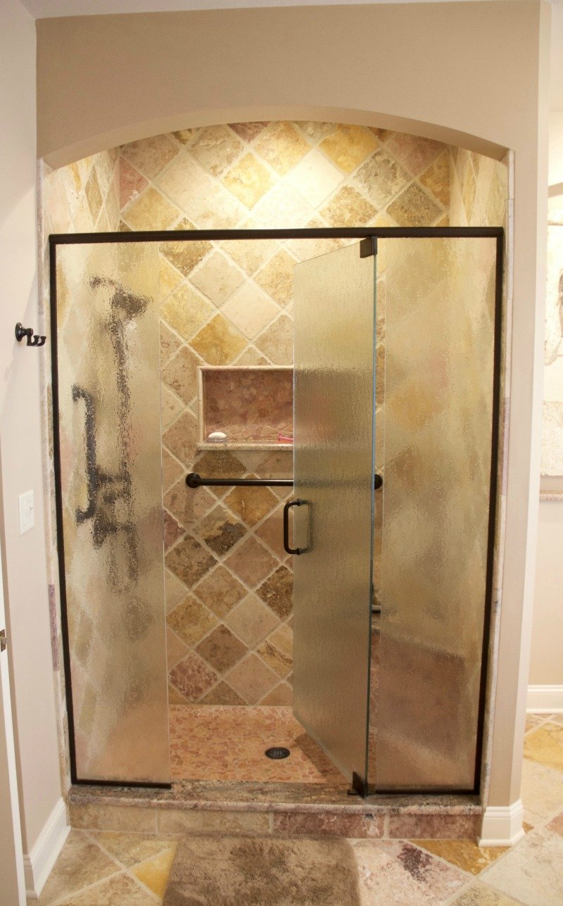 Framed embossed glass panels with a centered door provide easy access and privacy. Textured glass was used for this frameless pivot shower door. The glass is easy to clean, resists streaks and provides privacy.