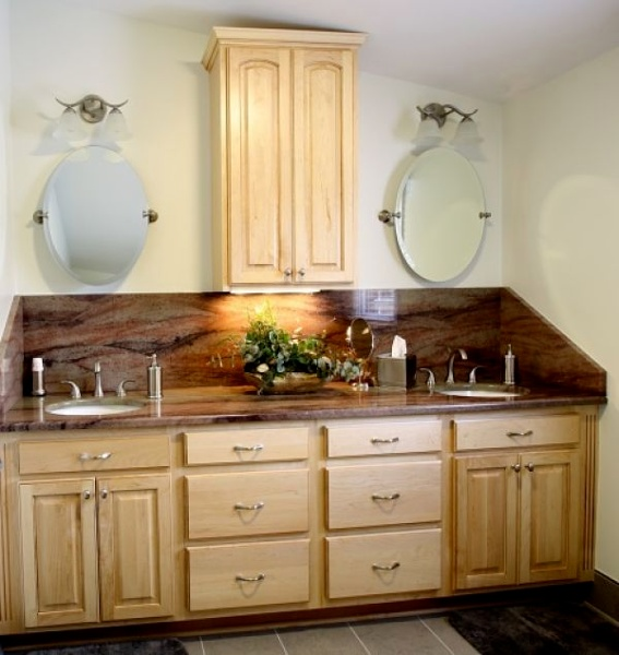 "A stunning slab of granite was the inspiration for the décor in this updated master bathroom. The granite was used for the counter of a double sink vanity. Under-mount sinks were selected to accentuate the stone. The wood cabinetry is from Jim Bishop and the finish is ""Natural Maple"". The vanity was made at a 34½ inches height rather than the standard 30 inches. The wall-mounted cabinet has under-cabinet lighting."