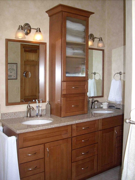 In this bathroom remodel, a storage tower provides space for towels and supplies and separates the dual sink vanity and framed mirrors. A stack of drawers separates the two base cabinets.