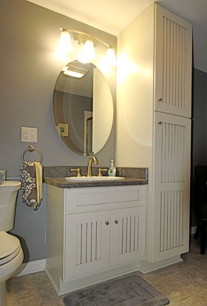 "Painted Jim Bishop cabinets in ""Off-white"" with an ""Oyster Gray"" glazed finish were used for the vanity and linen closet. An oval mirror with a beveled edge and an oval sink complement the vanity."