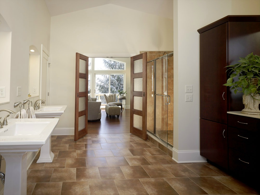 This stunning master bathroom features custom cherry cabinetry that provides ample storage space.