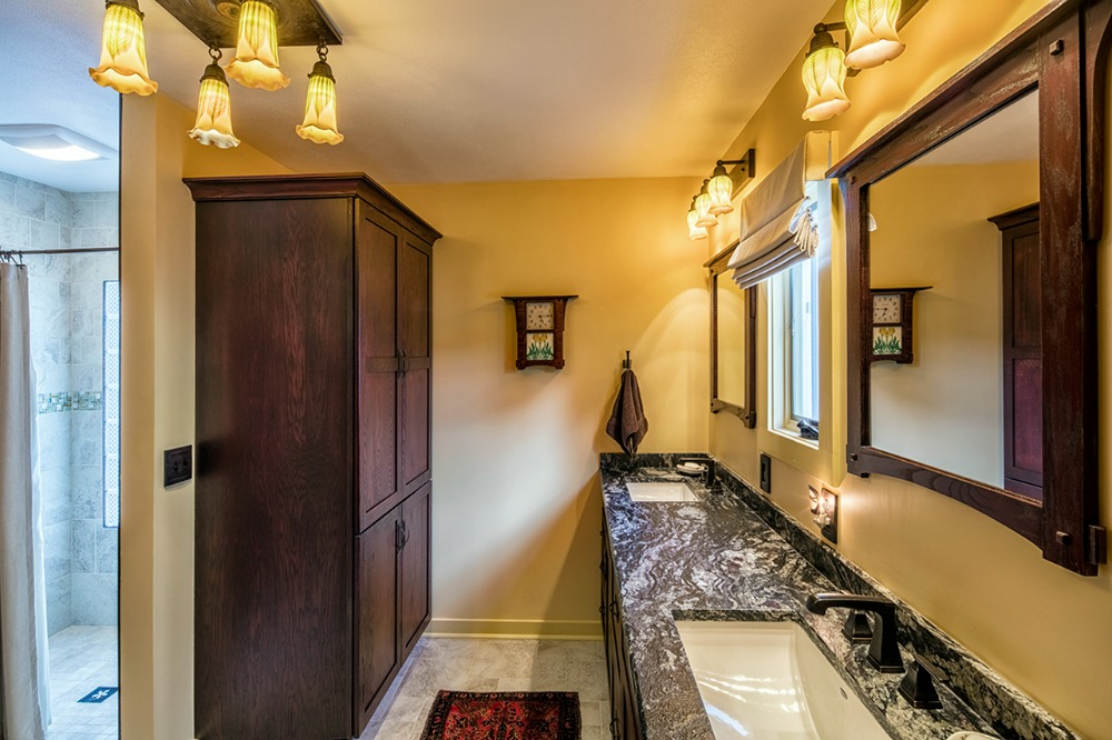 One of the two tall wardrobe cabinets, from Bishop Cabinets, is shown in this photo along with the stunning graphite granite vanity counter in a leather finish. Ample storage is provided in cabinet doors and drawers beneath the vanity. Art glass vanity lights were installed above the mirror and a ceiling fixture with four pendants provides general lighting in the room. The custom-built Craftsman-style mirrors were made from red oak.