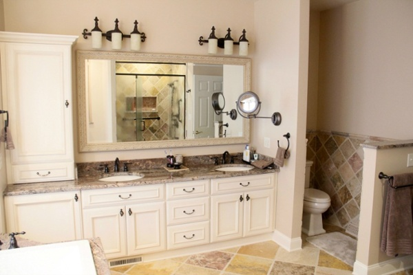 This master bathroom retreat was remodeled with many custom features that reflect the personal style of the homeowners. Storage was expanded in the room by adding a storage tower and base cabinets to the double-sink vanity. The vanity mirror is a custom designed mirror. Their choice of full overlay cabinets optimizes interior storage space.