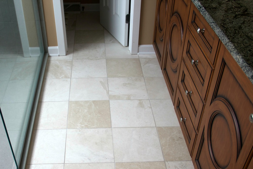 "Flooring features 12-by-12 inch ""Marble Botticino"" tile in a honed finish from Dobkin Tile. The heated flooring system and thermostat are from SunTouch."
