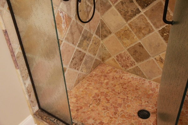 This custom tile shower base is crafted with colorful mosaic tile and a granite threshold.