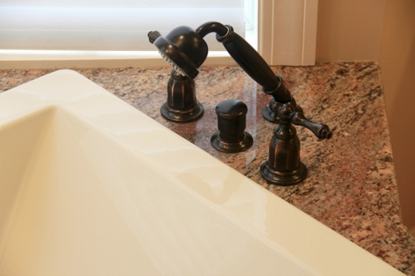 Kohler handheld shower spray and faucets were installed on the granite tub deck surface.