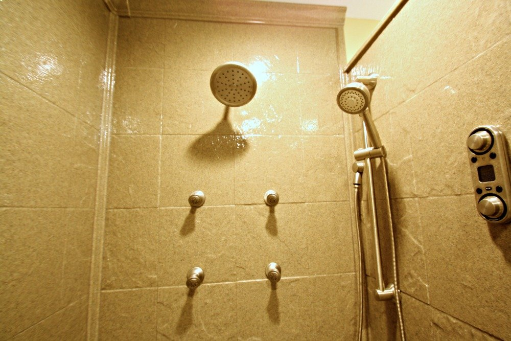 The wall jets and showerheads can be controlled by the Moen ioDigital unit at the right of the photo or by a remote.