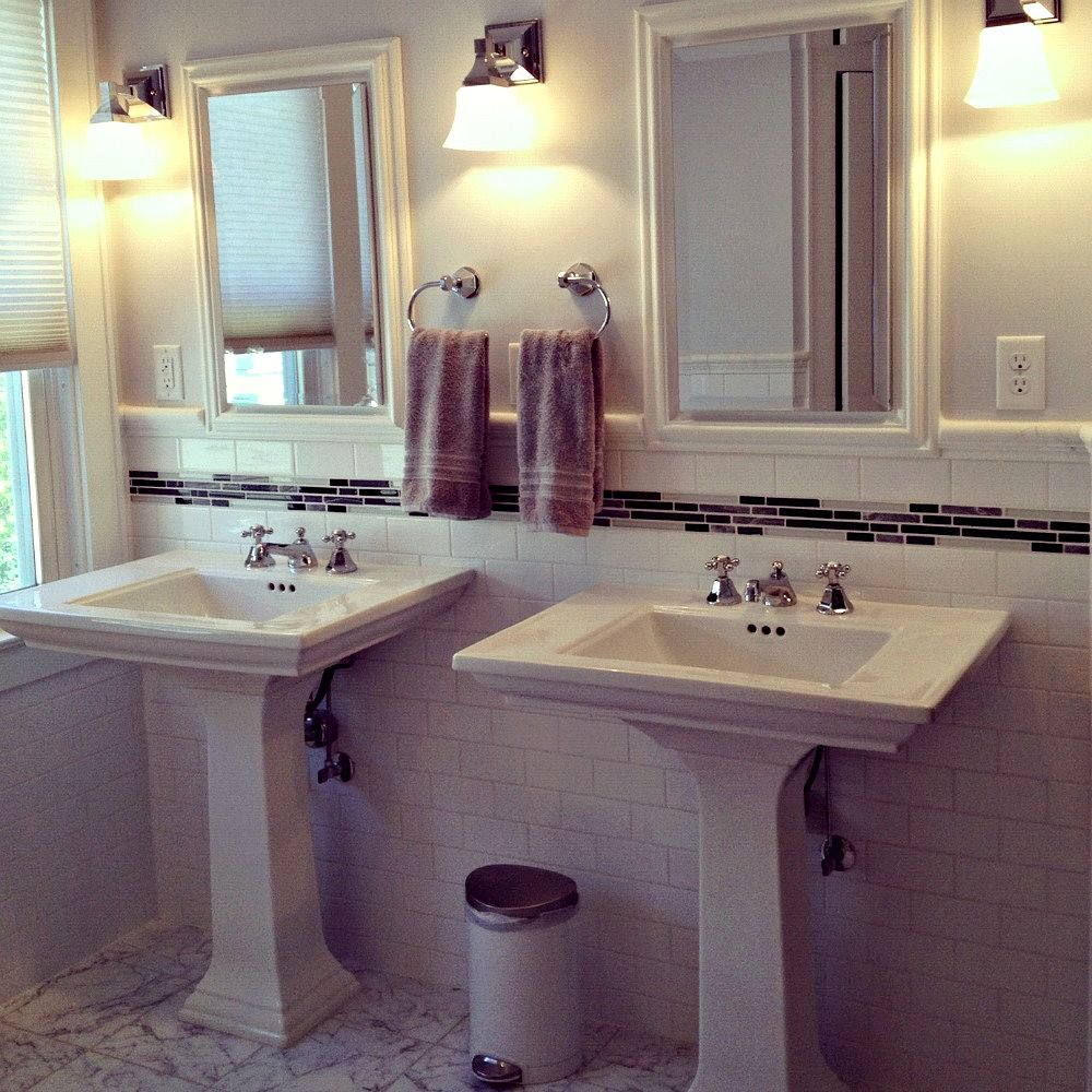 "Two pedestal sinks from the Kohler ""Memoirs"" Collection provide separate grooming areas for the homeowners and save space in the room. Sink fixtures are chrome from Mirabelle. Wall sconces are also from Mirabelle. The mirrored medicine cabinets above the sinks are recessed so they don't look like storage units."