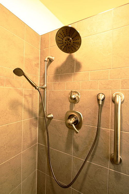 A rainfall showerhead with a lever-handled control and a handheld vertical mounted showerhead were selected. A small grab bar was installed for safety. Large wall tiles were used for easy maintenance.