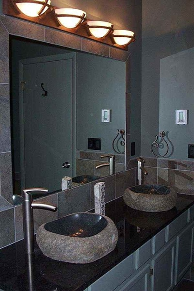 Unique surface mounted stone sinks that appear to be carved out polished gemstones are placed on a black granite countertop. Tall single-handle brushed stainless faucets, white cabinetry, stone look wall tiles and a contemporary vanity light fixture tie the room together.