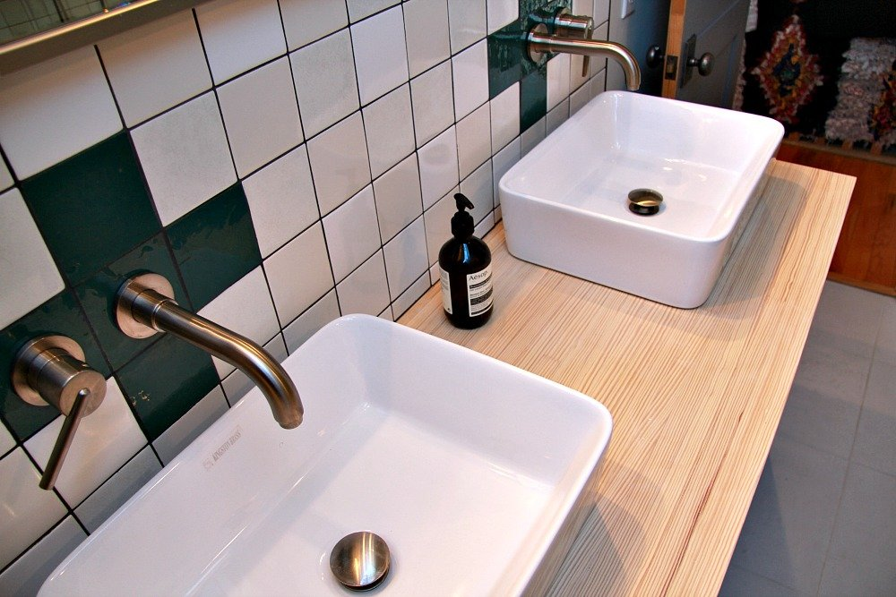 These white rectangular vessel sinks were mounted on the vanity. Single handle faucet fixtures were mounted in the wall.