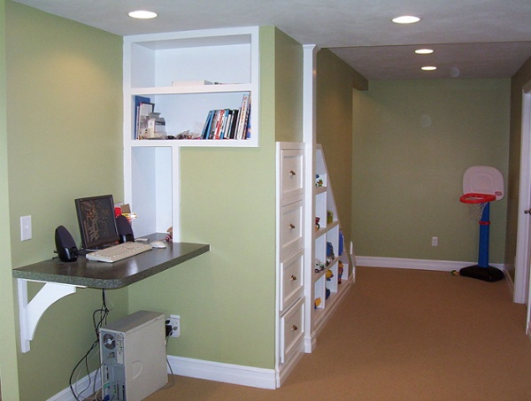 Cubbies and drawers were custom built underneath the stairs to this finished basement to create a place for toys and books to be neatly stored. A small countertop was installed to create a computer station.