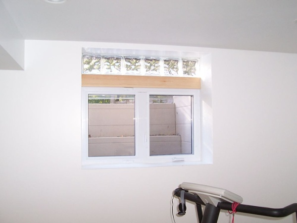 The interior side of this egress (exit) basement system allows more natural light and ventilation into the space. An attractive glass block transom adds style to this window.