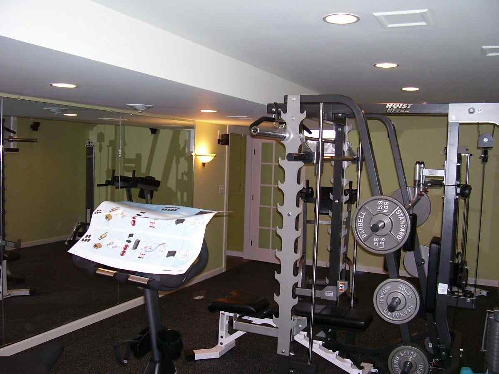 This basement finish was designed and constructed to accommodate the owner's exercise equipment. The wall of mirrors makes the room feel larger.