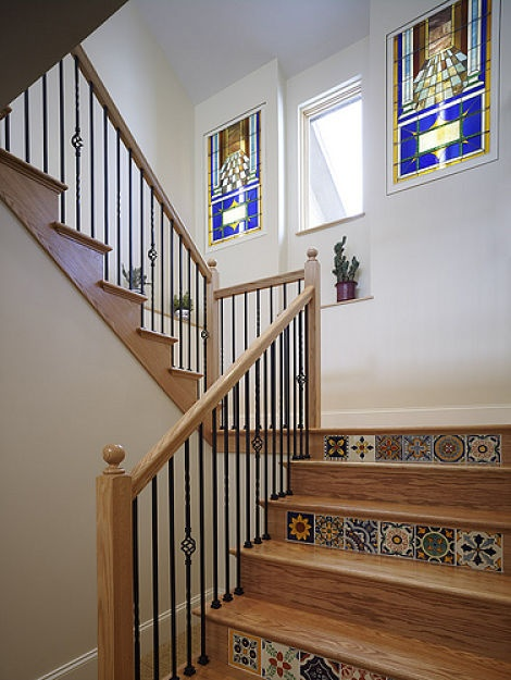 Tile from Spain inlaid into the risers and backlit stained glass add beauty and elegance to this unique custom staircase.