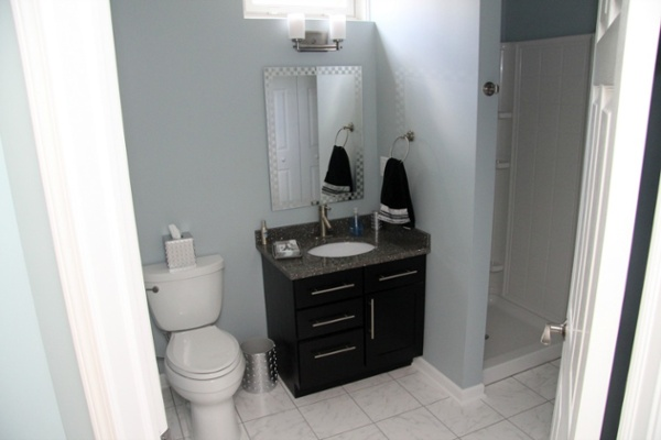 A window brings natural light into this basement bathroom and can be opened to provide ventilation. Flooring is slip-resistant tile. The Shaker-style vanity has a quartz surface and undermount sink. The mirror and uplight sconces add interest to the room. The homeowners also included a convenient walk-in shower.