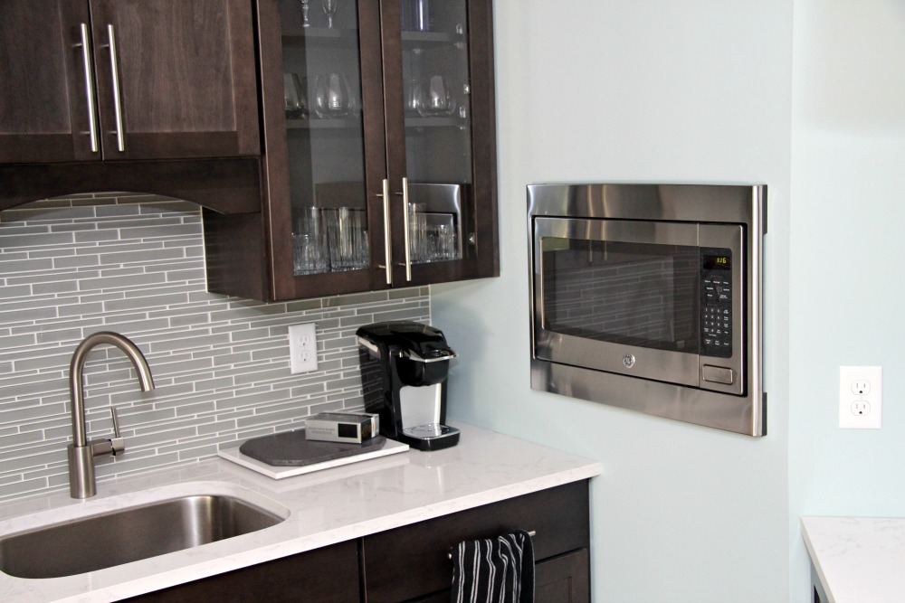 This basement kitchenette features dark stained cabinets, quartz counters, mosaic glass tile backsplash and a built-in microwave.