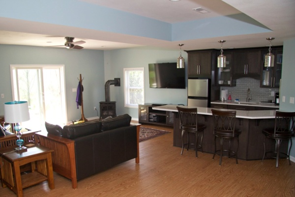 A coffered ceiling hides wires and plumbing in this lower level living space. Upscale vinyl flooring looks like wood and is easy to maintain. The kitchenette includes a bar area for food prep, serving and informal dining. A big screen TV is mounted on the wall for optimal viewing from the seating area. A corner gas fueled stove provides supplemental heat to the room and helps to lower humidity.