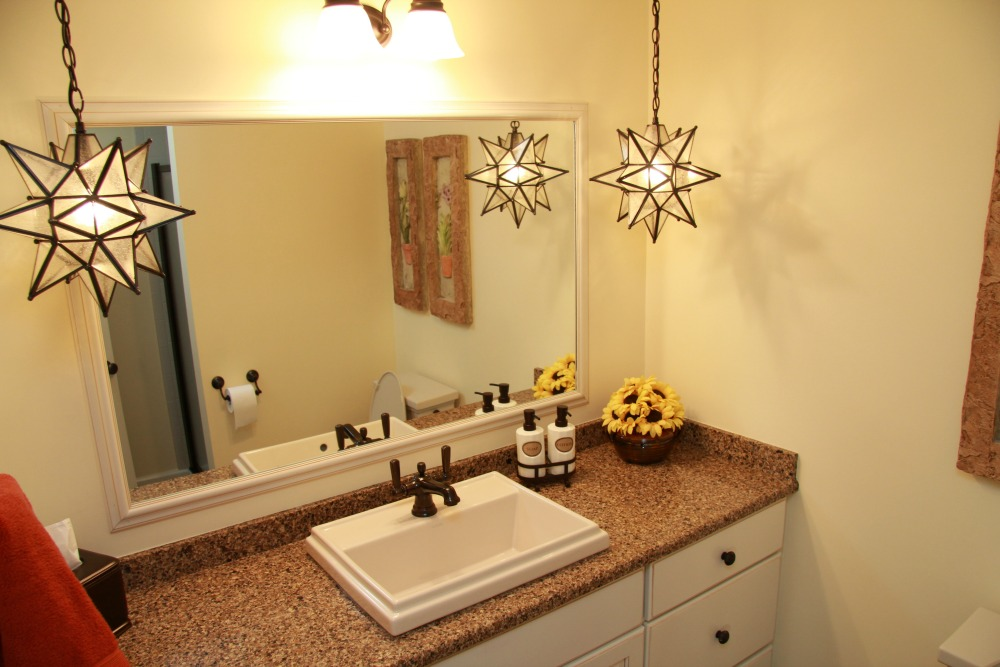 Star pendant lights add a whimsical accent to this lower level bath. A rectangular vessel sink matches the finish and lines of the mirror and cabinets.