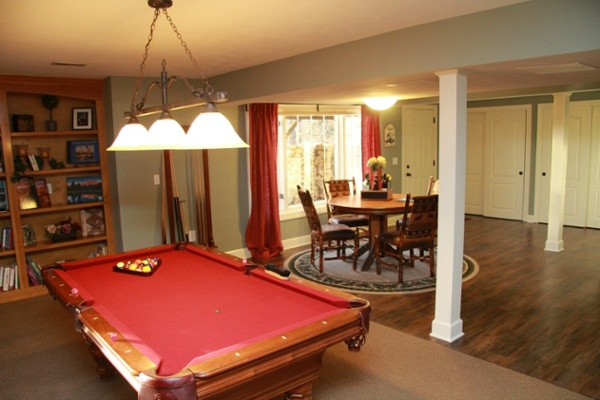 This lower level game room features a pool table. A three-lamp downlight hanging fixture was placed at a proper height to illuminate the surface of the table. There is also a rack on the wall to hold cues and carpeted flooring in the game area.