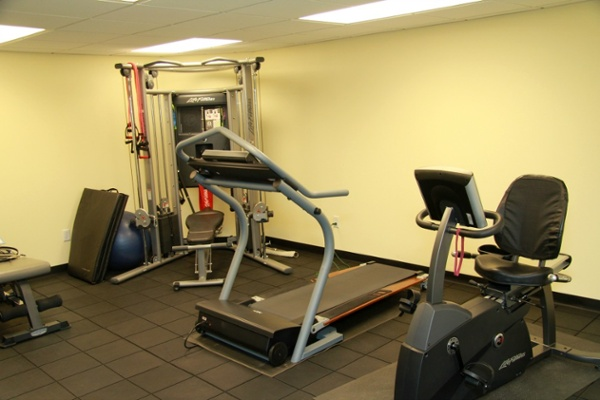 This lower level home gym includes a treadmill, universal, weight bench and an exercise bicycle. The specialized flooring provides cushioning for the exercise equipment. The ceiling has acoustical tile to provide access to mechanicals and quiet the sound during workouts.