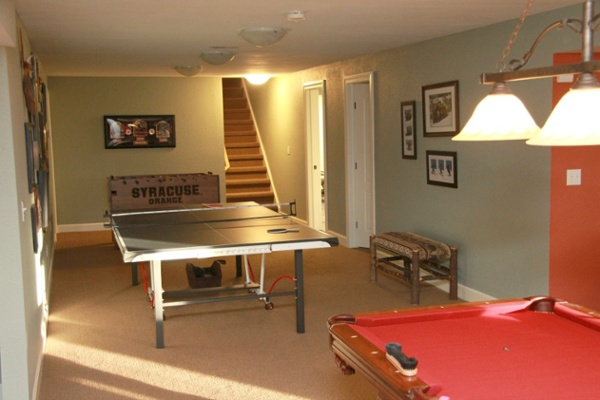 This lower level game room features a pool table and ping-pong table. Three ceiling mounted lights were installed to illuminate the surface of the ping-pong table and a three-lamp downlight hanging fixture was placed at a proper height to illuminate the pool table.