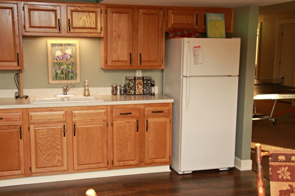 The kitchenette provides a space for preparing snacks and informal meals. Natural finish oak cabinets from Jim Bishop Cabinets were used. A Cambria countertop and backsplash are easy to clean. An undercabinet light illuminates the sink.