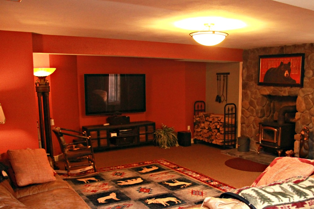 Walls in the theater area of this media room were painted red and new carpet was installed. A flat screen HD television is mounted on the wall of an alcove for optimal viewing and reduction of glare. A floor-to-ceiling stone wall and cast iron stove provide a focal point in the space.