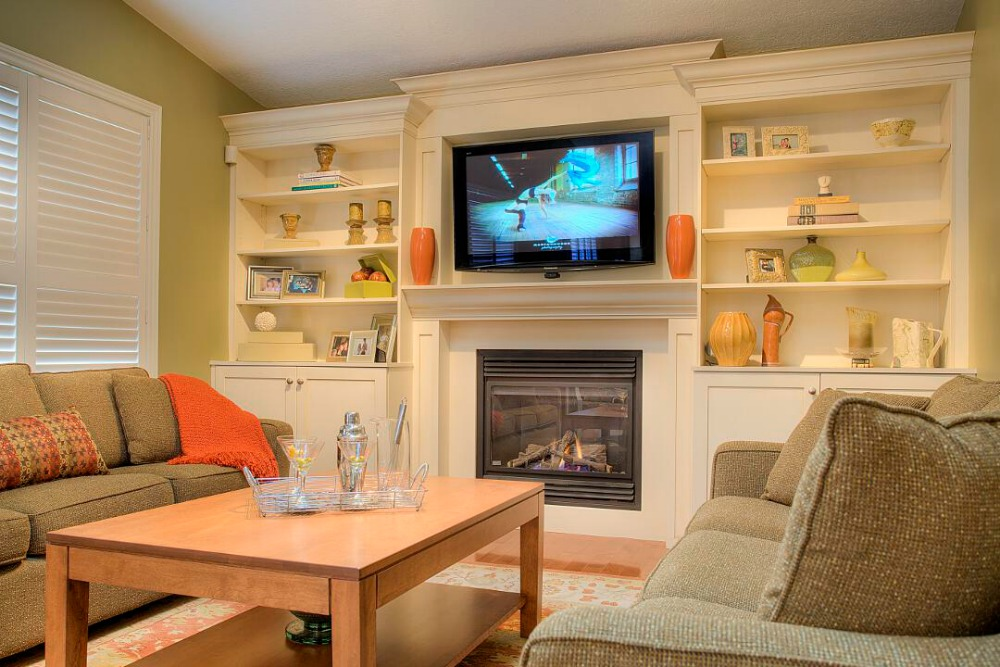 built in entertainment center encases a gas fireplace and a flat