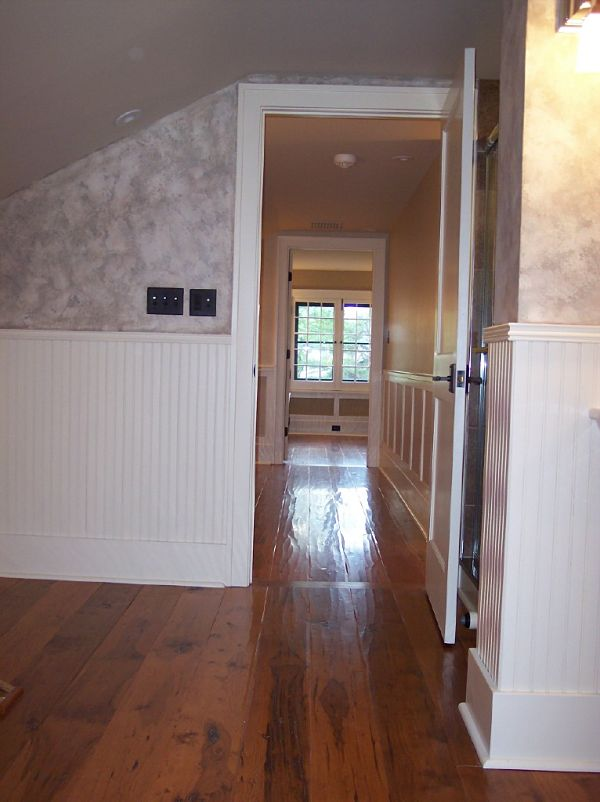 The painted beaded wainscot along with the distressed flooring in this 2nd floor remodel stays in tune with character of this older home.