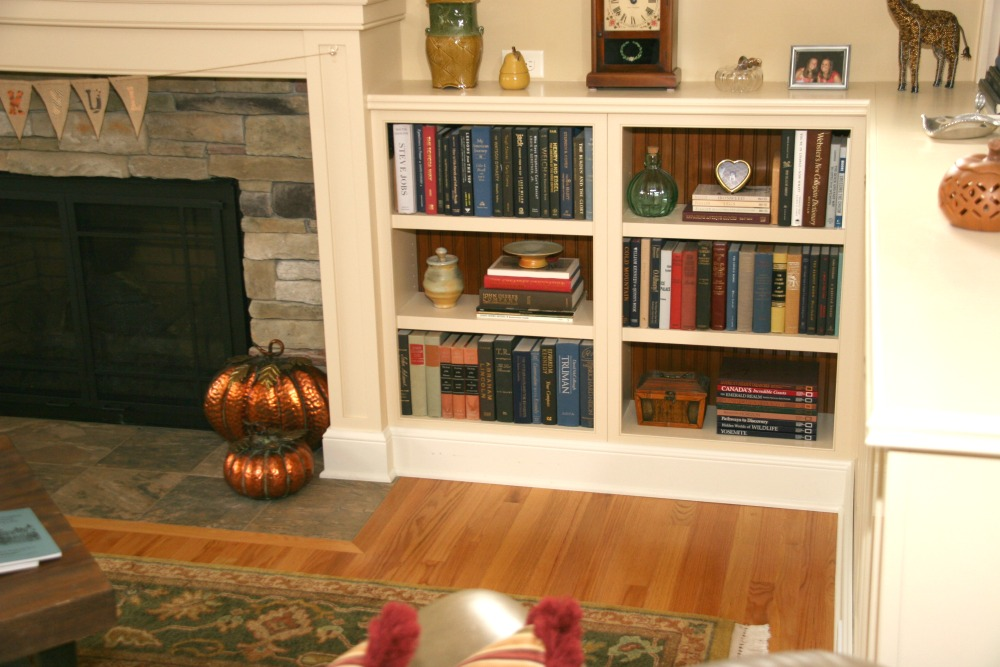 This family room fireplace has a stone surround and wood mantel with decorative molding that complements the bookcase.