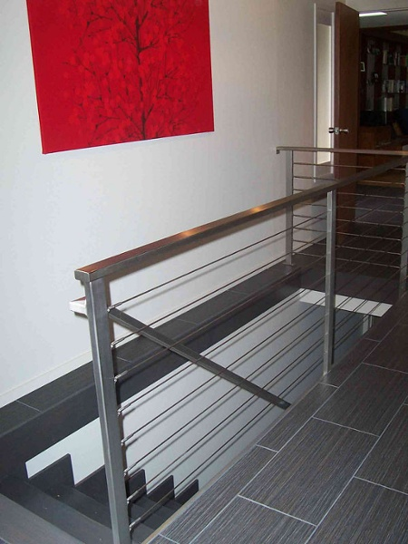 The options of railing selections are endless. For a contemporary look, an aluminum cable railing system was installed along with the unique 12-by-24 inch ceramic grooved tile.