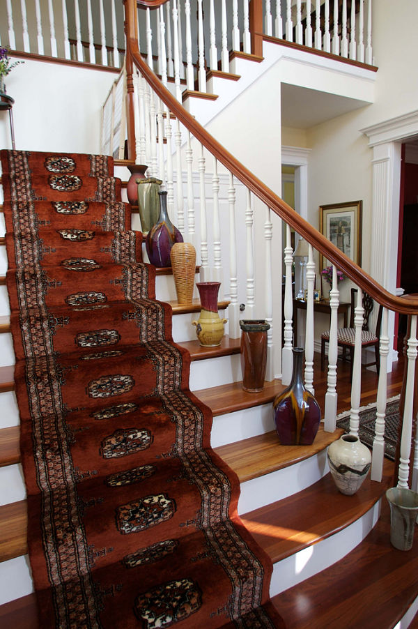 This custom curved stairway with carved banister accentuates the craftsmanship and ornate trim throughout the home.