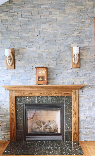 The fireplace wall was constructed with a ledger stone façade. The hearth was fashioned with granite tiles. The Mission Oak mantel was made to match a mantel owned by the homeowners. A new, deeper mantel was constructed to fit with the stone.