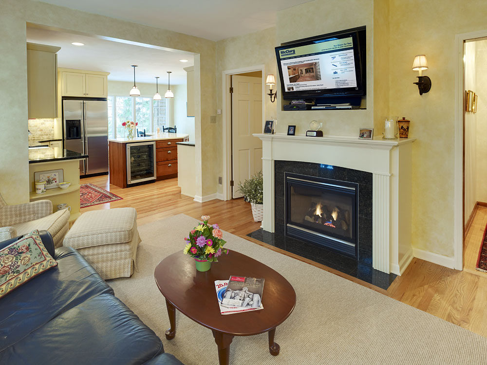 This fireplace features an oversized mantel, a gas fireplace insert and a granite tile surround and hearth. The white painted wood of the mantel, accented with carved wood columns and molding, blends with the interior of the home. The flat screen television that is recessed into the wall over the mantel augments the granite surround and hearth.