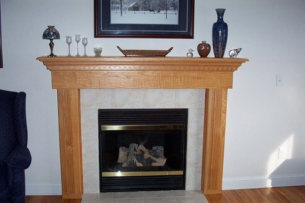 For an updated look, a custom oak mantel and new tile surround was installed for this gas fireplace. The grain of the wood stands out along with the dentil molding and carved columns to add architectural interest to this room.