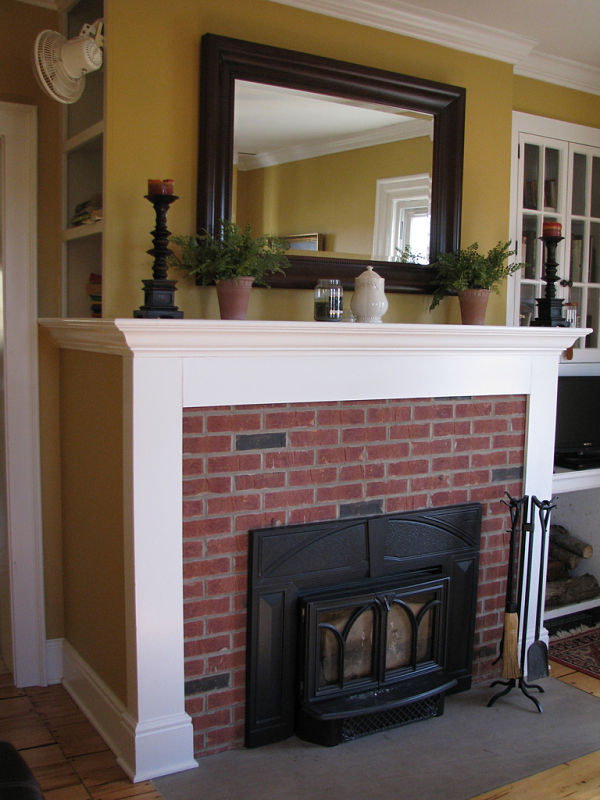 Here is a traditional fireplace with a brick surround, a cast iron stove insert and white painted wood mantel.