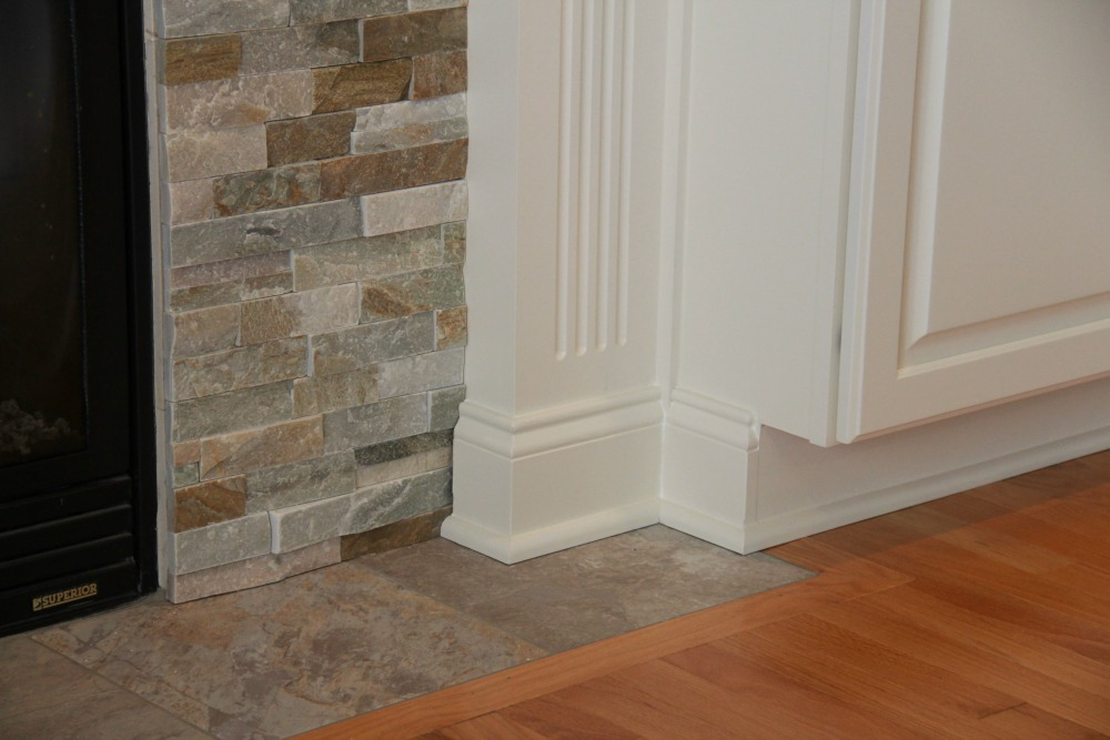 A dry stack stone veneer surround melds with the oak hardwood flooring and white painted cabinets and trim from Bishop Cabinets.